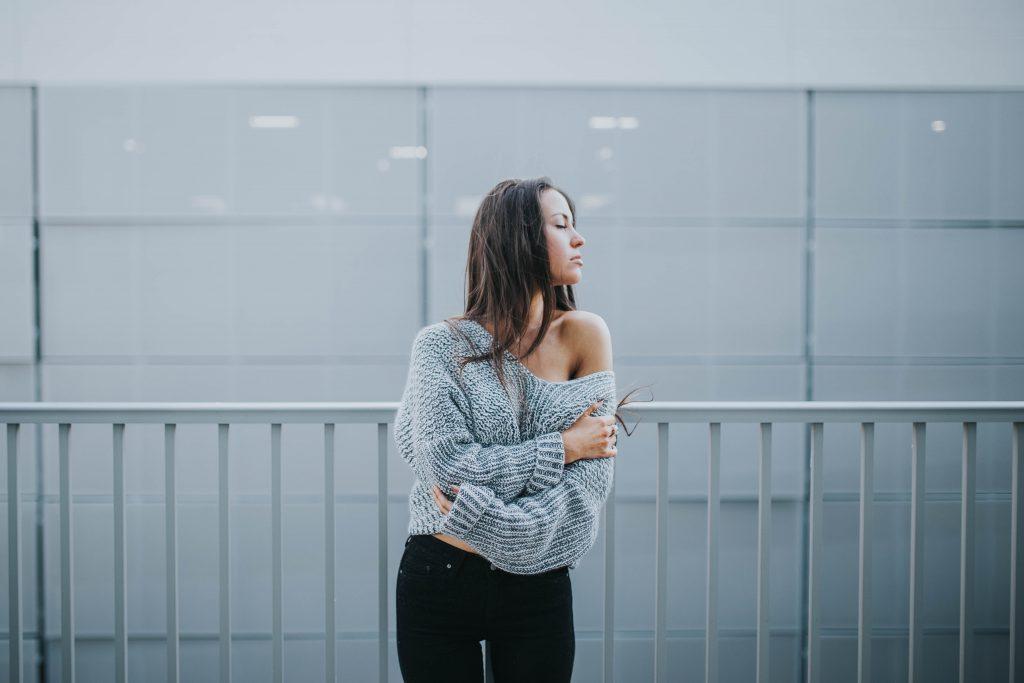 femme brune portant un pull gris laissant apparaitre une épaule et un pantalon noir