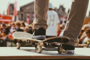 zoom sur les pieds d'un homme portant des baskets foncées et un pantalon chino beige avec un pied posé sur une skate