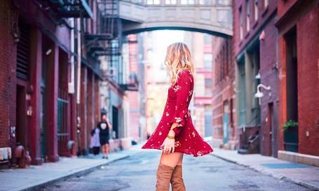 femme blonde portant une robe rouge courte et des cuissardes camel dans la rue