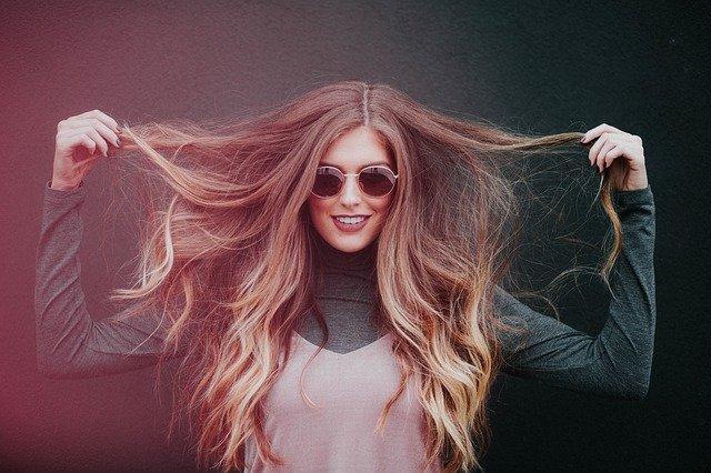 femme châtain qui sourie avec lunettes de soleil